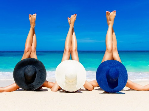 Three-young-women-in-straw-hats-lying-on-a-tropical-beach,-stretching-up-slender-legs.-Blue-sea-in-the-background.-Summer-vacation-concept.